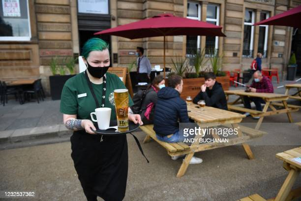 Hospitality worker carries a customers' drinks order to their outside tables at a re-opened Wetherspoons pub in Glasgow on April 26, 2021 following...