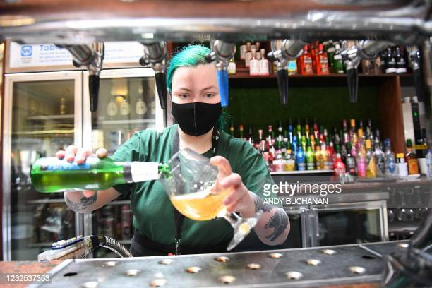 Hospitality worker prepares customers' drinks before taking them to their outside tables at a re-opened Wetherspoons pub in Glasgow on April 26, 2021...