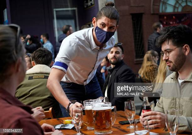 Hospitality worker serves a pitcher of beer to customers sat at an outdoor table of a re-opened bar in the Soho area of London, on April 16, 2021...