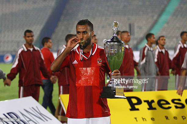 Hossam Ashur of AL Ahly poses with the trophy and kisses his medal after winning the football match between Al Ahly and Zamalek during Egypt Super...