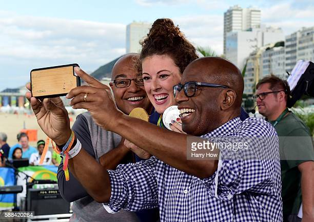 Host, Al Roker poses for a photo with swimmer, Allison Schmitt of the United States and broadcaster, Mike Tirico on the Today show set on Copacabana...