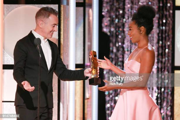 Host Alan Cumming presents Betty Gabriel the award for Best Ensemble at AARP's 17th Annual Movies For Grownups Awards at the Beverly Wilshire Four...