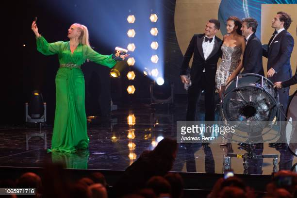 Host Barbara Schoeneberger takes a selfie together with Orlando Bloom Irina Shayk Patrick Dempsey and Henry Cavill on stage during the GQ Men of the...