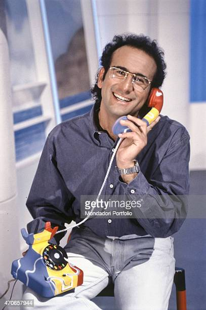 'TV host Carlo Conti holds the handset of a telephone set painted in blue yellow and red posing on the studio of the kids entertainment broadcast...