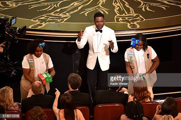 Host Chris Rock and Girl Scouts sell cookies to audience members during onstage during the 88th Annual Academy Awards at the Dolby Theatre on...
