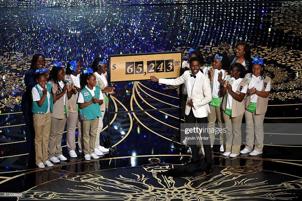 Host Chris Rock (C) presents the amount of money collected during the show by the Girl Scouts, including Rock's daughters Zahra and Lola, onstage at the 88th Annual Academy Awards at the Dolby Theatre on February 28, 2016 in Hollywood, California.