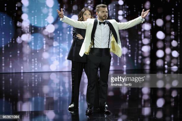 Host Edin Hasanovic and President of the German Film Academy Iris Berben perform on stage during the Lola German Film Award show at Messe Berlin on...