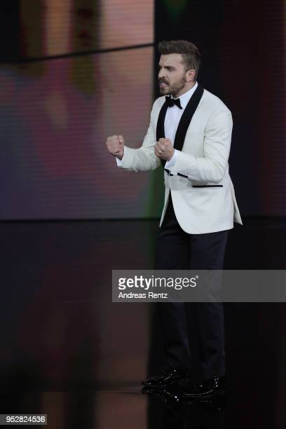 Host Edin Hasanovic gestures on stage during the Lola German Film Award show at Messe Berlin on April 27 2018 in Berlin Germany