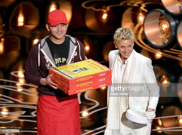 Host Ellen DeGeneres with pizza delivery man onstage during the Oscars at the Dolby Theatre on March 2 2014 in Hollywood California
