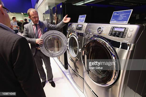 A host explains the functions of new energyefficient washing machines at the Samsung home appliances stand at the 2010 IFA technology trade fair at...