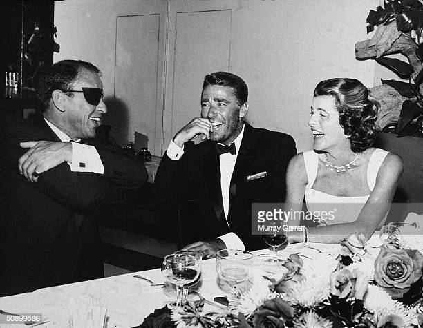 Host Frank Sinatra wears an eyepatch laughing with actor Peter Lawford and his wife Patricia Kennedy during a surprise 21st birthday party held for...