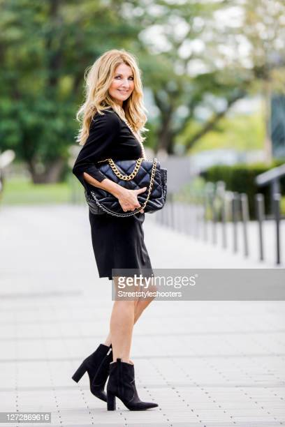 Host Frauke Ludowig, wearing a black dress by Ancora, long chains by Celia von Barchewitz, black booties by Steve Madden and a black bag by Chanel...
