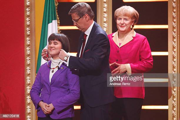 TV host Guenther Jauch takes off a necklace from the Angela Merkel wax figure and hands over to Maria Zanchetta during 2014 Menschen Bilder Emotionen...