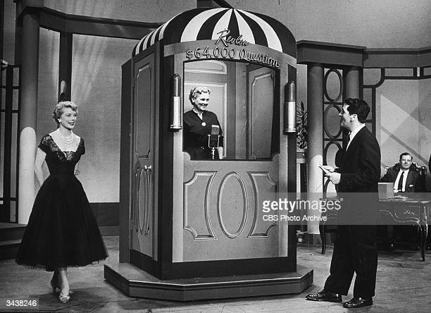 Host Hal March questions a contestant inside a booth during the television quiz game show, 'The $64,000 Question,' 1955.