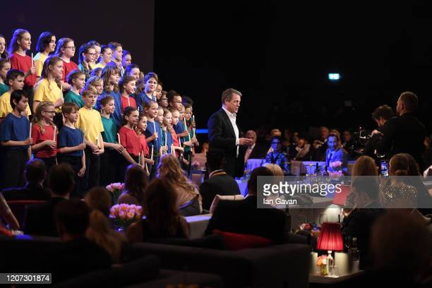 Host Hugh Grant with the choir during the 2020 Laureus World Sports Awards at Verti Music Hall on February 17 2020 in Berlin Germany