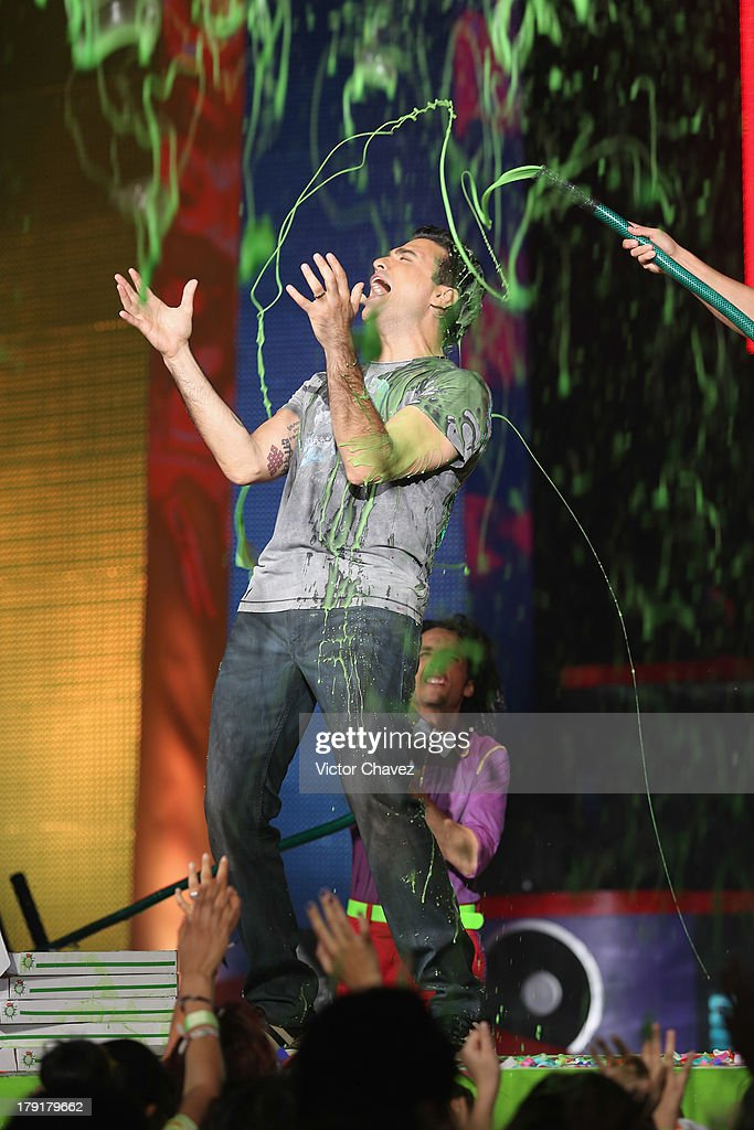 Host Jaime Camil speaks onstage after getting slimed during the Kids Choice Awards Mexico 2013 at Pepsi Center WTC on August 31, 2013 in Mexico City, Mexico.