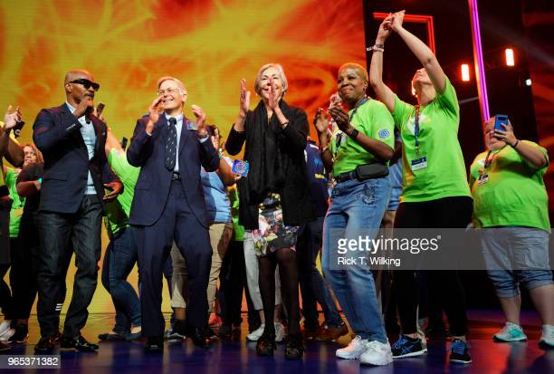 Host Jamie Foxx dances onstage with Jim Walton CEO Arvest Bank Group Inc and sister Alice Walton and Walmart associates during the annual...