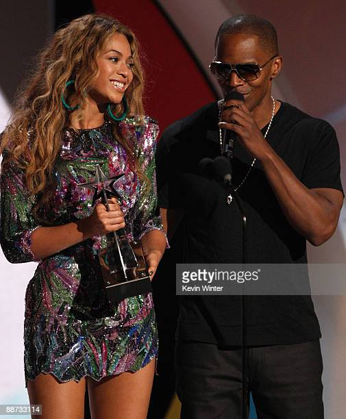 Host Jamie Foxx escorts singer Beyonce to her seat after she accepted the Best Female RB Artist award onstage during the 2009 BET Awards held at the...