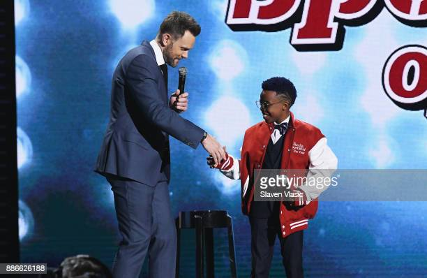 Host Joel McHale presents Bunchie Young with the SI Kids Sportskid of the Year Award during SPORTS ILLUSTRATED 2017 Sportsperson of the Year Show on...