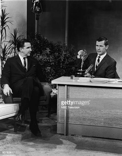 Host Johnny Carson sits with an Emmy award on his desk as announcer Ed McMahon looks on in a still from 'The Tonight Show With Johnny Carson' 1963