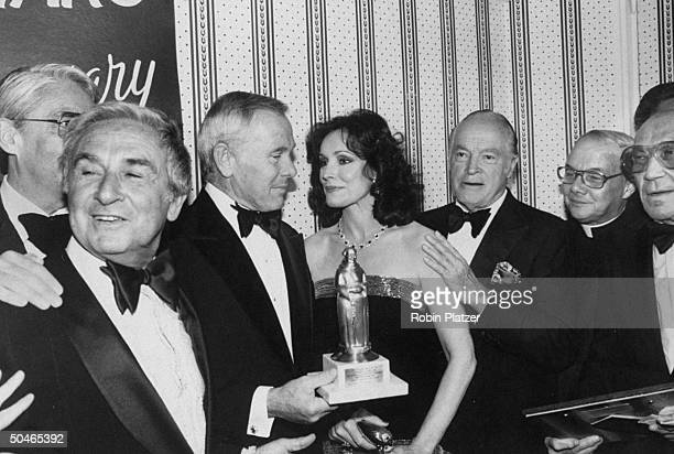 TV host Johnny Carson w third wife Joanna holding Friars Club Entertainer of the Yr award as Bob Hope and Rev Robert O'Connell look on