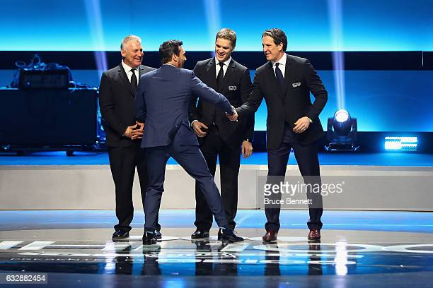 Host Jon Hamm greets former NHL players Brett Hull Luc Robitaille and Brendan Shanahan on stage during the NHL 100 presented by GEICO Show as part of...