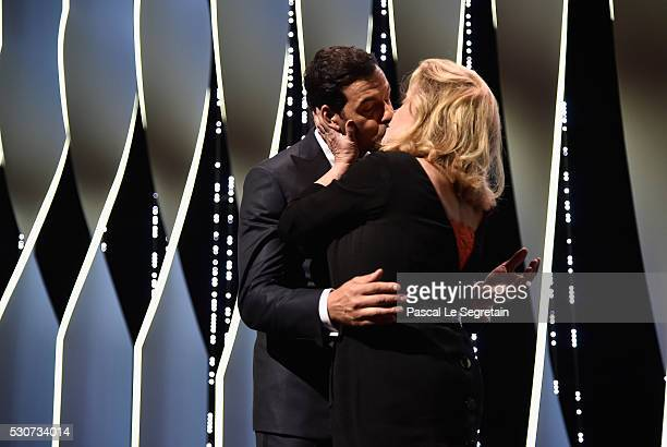 Host Laurent Lafitte and Actress Catherine Deneuve kiss on stage at the Opening Gala Ceremony during The 69th Annual Cannes Film Festival on May 11...