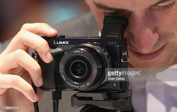 A host looks through a Lumix GX7 digital camera on display at the Panasonic stand at the IFA 2013 consumer electronics trade fair on September 5 2013...