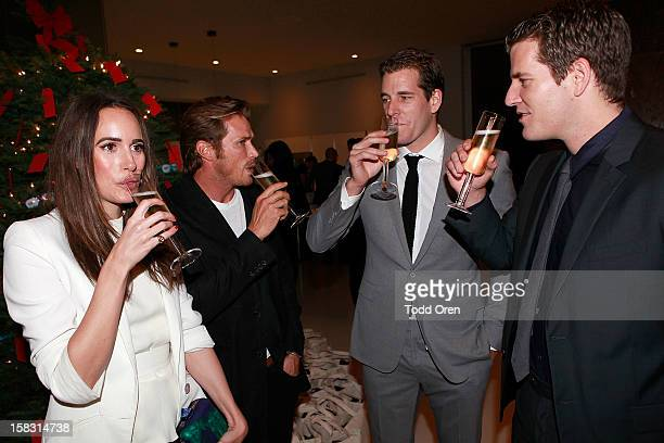 Host Louise Roe Actor Jason Lewis Cameron Winklevoss and Tyler Winklevoss toast at the Hukkster Holiday Party Hosted by Louise Roe and Founders Katie...