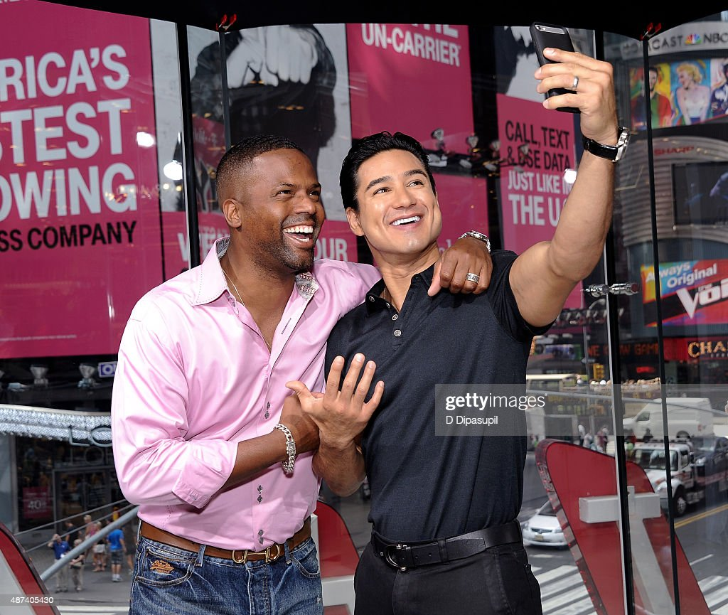 Host Mario Lopez (R) and correspondent AJ Calloway pose for selfie on the set of 'Extra' at their New York studios at H&M in Times Square on September 9, 2015 in New York City.