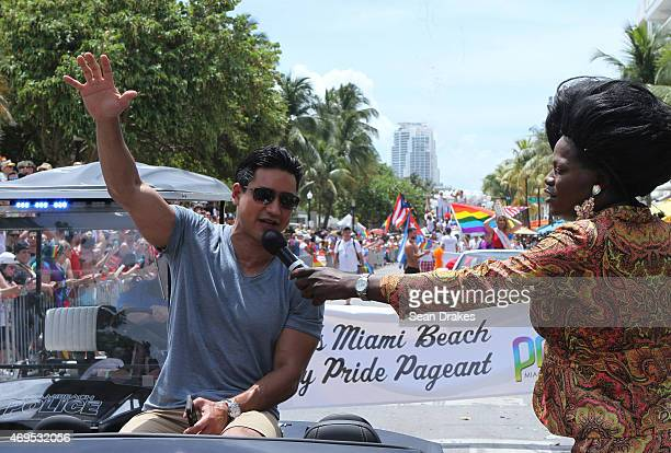 TV host Mario Lopez speaks to the audience as drag queen performer Tiffany Fantasia hands him the microphone while he serves as Grand Marshal for the...
