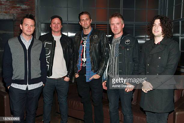 Host Mark Hoppus poses for photos with Tom DeLonge David Kennedy Matt Wachter and Ilan Rubin of the band 'Angels And Airwaves' during a taping of...