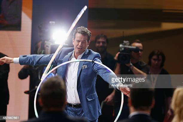 TV host Markus Lanz perfoms with a hula hoop during the 'Wetten dass' tv show on April 5 2014 in Offenburg Germany