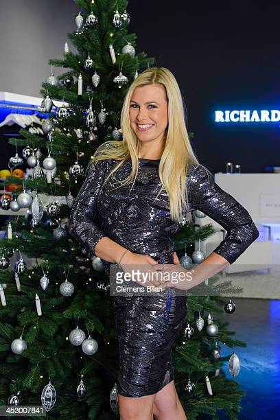 Host Nadine Krueger poses during a photo session in front of a christmas tree at fashion designer Richard Kravetz's venue on December 01, 2013 in...