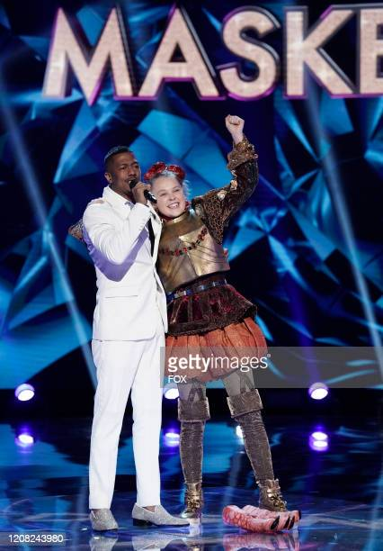 Host Nick Cannon and Jo Jo Siwa in the Old Friends New Clues Group C Championships episode of THE MASKED SINGER airing Wednesday March 25 on FOX