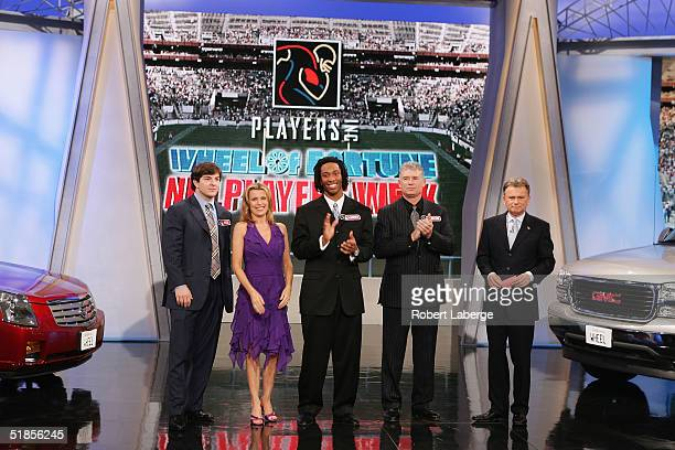 Host Pat Sajak stands with Washington Redskins Hall of Fame running back John Riggins Larry Fitzgerald of the Arizona Cardinals CoHost Vanna White...