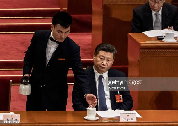 A host refills the tea cup of China's President Xi Jinping after a vote on an amendment to the constitution during a session of the National People's...