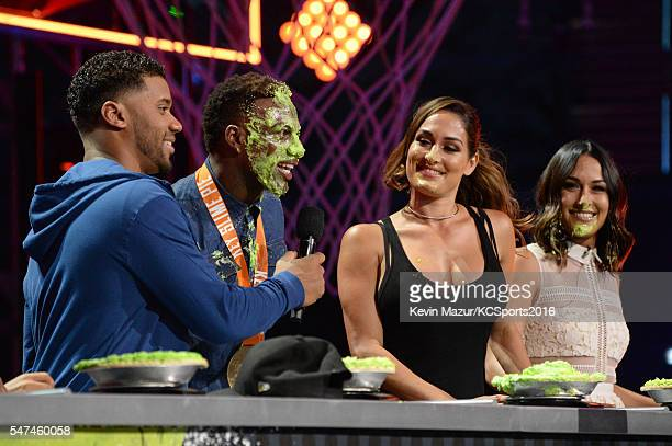 Host Russell Wilson NFL player Emmanuel Sanders and professional wrestlers Nikki Bella and Brie Bella participate in a key slime pie eating contest...