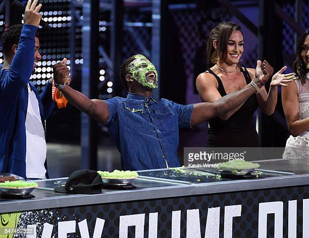 Host Russell Wilson NFL player Emmanuel Sanders and WWE personality Nikki Bella participate in a pieeating contest onstage during the Nickelodeon...