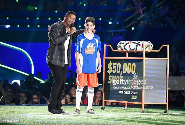 Host Russell Wilson prepares Roee Maor to comepete in the $50,000 Shot onstage at the Nickelodeon Kids' Choice Sports Awards 2015 at UCLA's Pauley...