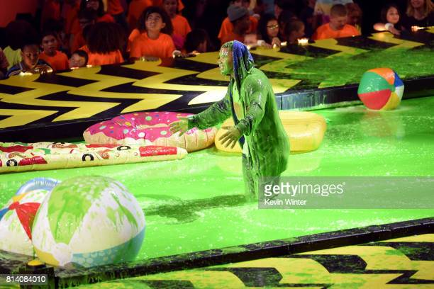 Host Russell Wilson stands in slime pool onstage during Nickelodeon Kids' Choice Sports Awards 2017 at Pauley Pavilion on July 13 2017 in Los Angeles...