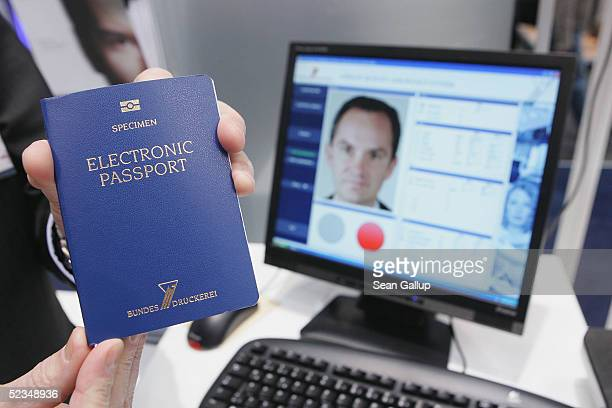 A host shows off a sample of the new German electronic passport that contains a computer chip to store biometric data at the CeBIT technology trade...