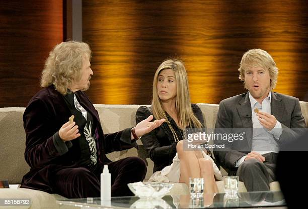 Host Thomas Gottschalk, actors Jennifer Aniston and Owen Wilson eat dog cakes as part of a challenge during the Wetten dass...? show at the Messe...