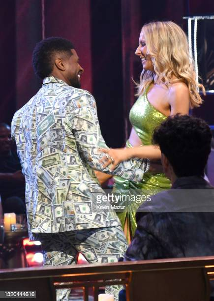 Host Usher and Nikki Glaser speak onstage at the 2021 iHeartRadio Music Awards at The Dolby Theatre in Los Angeles, California, which was broadcast...