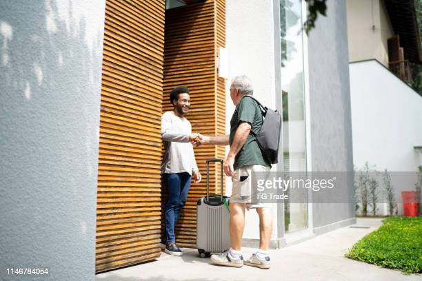 host welcoming his guest in the doorway - sharing economy stock pictures, royalty-free photos & images