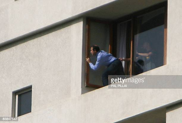 A hostage peeks from a window of the Trident hotel where hostages are being held by gunmen in Mumbai on November 28 2008 Up to 130 people were killed...