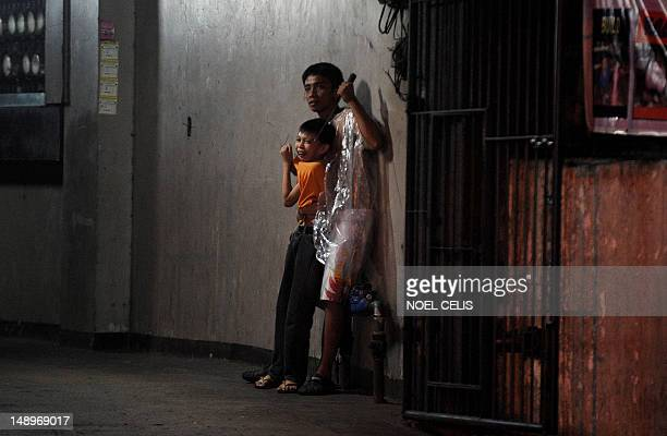 Hostage taker Remer Parparan points an icepick at 10 years old Jason Pineda during a hostage taking incident in Manila on July 21 2012 The three hour...