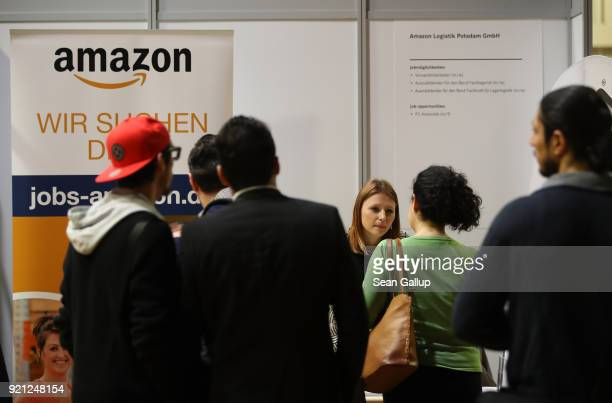 A hostess at a stand of online retailer Amazon explains employment opportunities to job seekers at the annual jobs fair for refugees and migrants at...