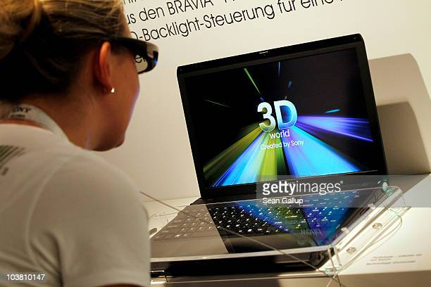 A hostess at the request of the photographer looks through 3D glasses at the prototype of a Sony 3D laptop computer at the Sony stand at the 2010 IFA...