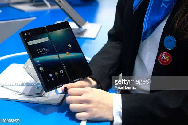 Hostess demonstrates the foldable dual-screened ZTE Axon M smartphone during the Mobile World Congress , the world's biggest mobile fair, on February...